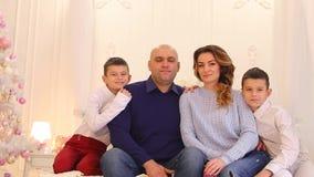 O retrato bonito da família moderna e loving, dois irmãos gêmeos e os pais de inquietação estão sentando-se na cama no quarto com vídeos de arquivo