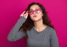 O retrato bonito da jovem mulher faz o beijo do voo, levantando no fundo cor-de-rosa, o cabelo encaracolado longo, óculos de sol  Imagem de Stock Royalty Free