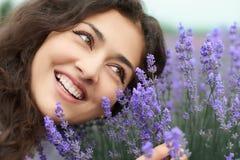 O retrato bonito da jovem mulher na alfazema floresce o fundo, close up da cara Imagens de Stock