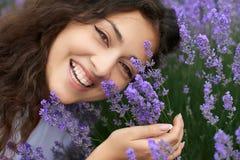 O retrato bonito da jovem mulher na alfazema floresce o fundo, close up da cara Foto de Stock Royalty Free