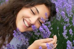 O retrato bonito da jovem mulher na alfazema floresce o fundo, close up da cara Imagens de Stock Royalty Free