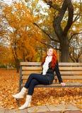 O retrato bonito da moça senta-se no banco no parque e relaxa-se, as folhas no outono, ruivo do amarelo, cabelo longo Foto de Stock Royalty Free