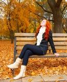 O retrato bonito da moça senta-se no banco no parque e relaxa-se, as folhas no outono, ruivo do amarelo, cabelo longo Fotografia de Stock Royalty Free