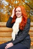 O retrato bonito da moça senta-se no banco no parque, folhas no outono, ruivo do amarelo, cabelo longo Foto de Stock
