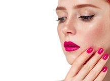 O retrato bonito da mulher com perfeito compõe os bordos e pregos vermelhos do tratamento de mãos foto de stock