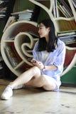 O retrato chinês da mulher bonita nova escuta a música na livraria Imagens de Stock Royalty Free
