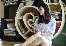 O retrato chinês da mulher bonita nova escuta a música na livraria Fotografia de Stock Royalty Free
