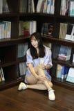 O retrato chinês da mulher bonita nova escuta a música na livraria Imagem de Stock