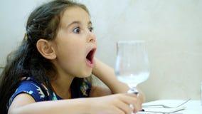 O retrato, close-up, menina bonita da criança, morena encaracolado-de cabelo contorce ao sentar-se em uma tabela em um restaurant vídeos de arquivo