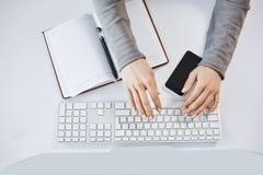 O retrato colhido da mulher entrega a datilografia no teclado e o trabalho com computador e dispositivos Freelancer fêmea moderno imagem de stock