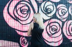 O retrato colorido da mulher loura consideravelmente nova que levanta em grafittis mura o fundo no vestido preto Fotografia de Stock