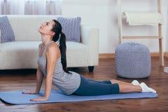 O retrato completo da opinião lateral do comprimento da jovem mulher bonita que dão certo em casa, fazendo a ioga ou os pilates e imagem de stock