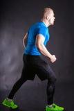O retrato completo do comprimento do corredor muscular do homem novo nos esportes equipa steping Imagem de Stock Royalty Free
