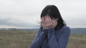 O retrato comprimiu a moça que grita e que cobre sua cara com suas mãos vídeos de arquivo