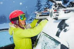 O retrato da asseguração da menina esquia às barras do ` s do telhado do carro fotos de stock