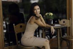 O retrato da beleza de uma mulher graciosa, fica em uma mesa de centro na cidade velha de Grécia imagem de stock