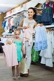 O retrato da compra da mulher e da menina caçoa o fato no sto da roupa Fotos de Stock Royalty Free