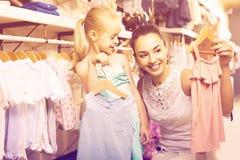 O retrato da compra da mulher e da menina caçoa o fato no sto da roupa Foto de Stock