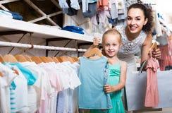 O retrato da compra da mulher e da menina caçoa o fato no sto da roupa Fotografia de Stock Royalty Free