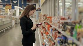 O retrato da compra positiva da menina da mulher conserva o molho de tomate dos pimentões quentes ou o vinagre balsâmico na loja  Fotos de Stock Royalty Free