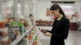 O retrato da compra positiva da menina da mulher conserva o molho de tomate dos pimentões quentes ou o vinagre balsâmico na loja  Imagens de Stock Royalty Free