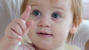 O retrato da criança fêmea curiosa pequena com os olhos cinzentos grandes bonitos aponta o close up do dedo vídeos de arquivo