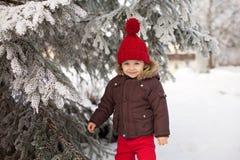 O retrato da criança no revestimento marrom e no vermelho fez malha o chapéu e o tr vermelho fotografia de stock