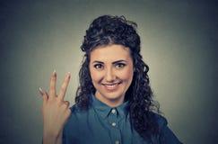 O retrato da doação bonita nova da mulher três dedos assina o gesto fotografia de stock