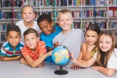 O retrato da escola caçoa a vista do globo na biblioteca foto de stock