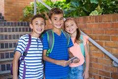 O retrato da escola de sorriso caçoa a posição na escadaria da escola fotografia de stock royalty free