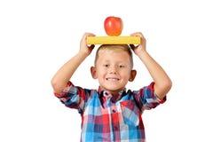 O retrato da estudante feliz com livro e da maçã em sua cabeça isolou o fundo branco Educação fotografia de stock royalty free