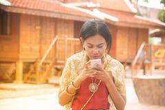 O retrato da fêmea asiática em vestidos tradicionais levanta o móbil do uso foto de stock