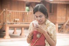 O retrato da fêmea asiática em vestidos tradicionais levanta o móbil do uso fotos de stock