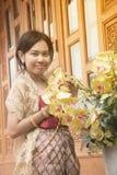 O retrato da fêmea asiática em vestidos tradicionais levanta na casa tailandesa imagens de stock royalty free
