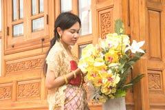 O retrato da fêmea asiática em vestidos tradicionais levanta na casa tailandesa fotografia de stock royalty free