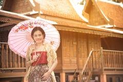 O retrato da fêmea asiática em vestidos tradicionais levanta na casa tailandesa foto de stock