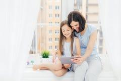 O retrato da fêmea bonita abraça sua filha pequena, desenhos animados do relógio na tabuleta digital, conectada ao Internet sem f foto de stock
