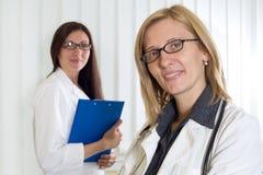 O retrato da fêmea dois segura de sorriso medica Looking na câmera sobre o fundo branco Foto de Stock