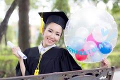 O retrato da fêmea nova feliz gradua-se no vestido acadêmico Imagens de Stock Royalty Free