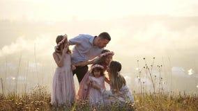 O retrato da família feliz com seus doughters senta-se no prado filme