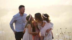 O retrato da família feliz com seus doughters senta-se no prado vídeos de arquivo