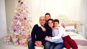 O retrato da família feliz e feliz, duas crianças do ` s do irmão e os pais loving sentam-se na cama no quarto com árvore festiva filme