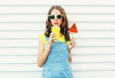 O retrato da forma a menina consideravelmente que fresca bebe um suco do copo guarda o gelado da melancia da fatia fotografia de stock royalty free