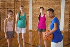 O retrato da High School caçoa a posição com basquetebol Fotografia de Stock Royalty Free