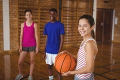 O retrato da High School de sorriso caçoa a posição com basquetebol Fotografia de Stock