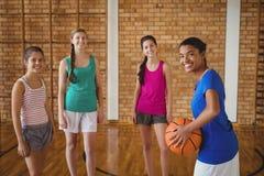 O retrato da High School de sorriso caçoa a posição com basquetebol Imagens de Stock Royalty Free
