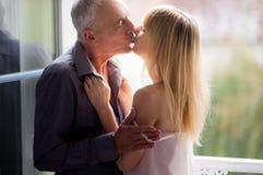 O retrato da jovem mulher atrativa que beija seu marido superior próximo abriu Windows na sala durante horas de verão idade Fotos de Stock