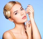 O retrato da jovem mulher bonita aplica o gelo à cara Fotos de Stock Royalty Free