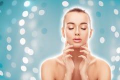 O retrato da jovem mulher bonita com pele limpa, fresca toca em sua cara na luz - fundo azul do bokeh Fotos de Stock