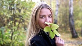 O retrato da jovem mulher bonita guarda a folha na floresta em cores da queda movimento 4k lento 3840x2160 video estoque